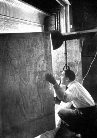 Howard Carter peers into the shrines holding the sarcophagi of Tutankhamun